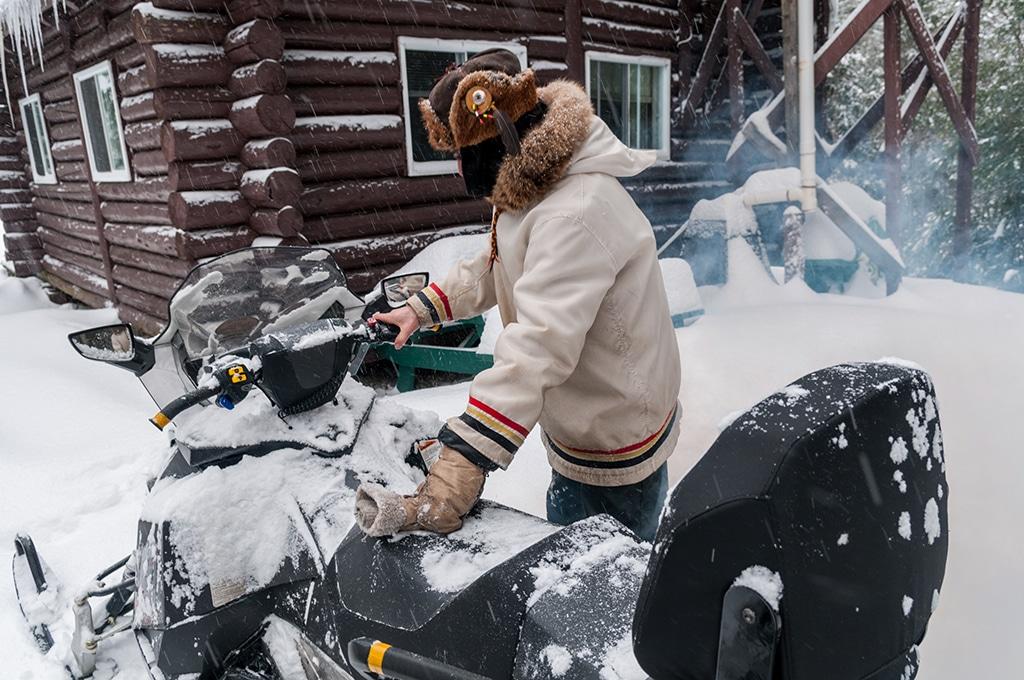 Canada, Quebec, Mauricie, région de Saint-Alexis-les-Monts, Pourvoirie du Lac Blanc l'hiver, Pierre trappeur indien algonquin devant chalet rustique