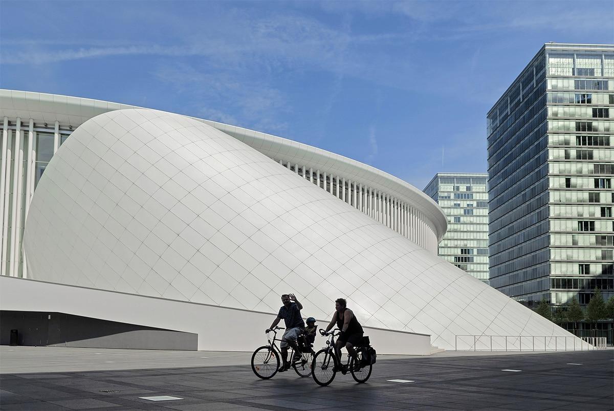 City-break au Luxembourg, famille en vélo devant le bâtiment du Philarmonique
