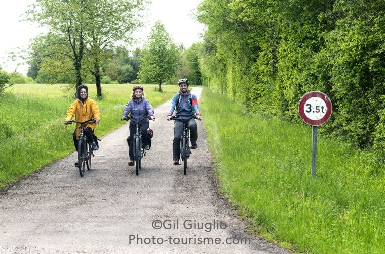 3 cyclistes sur petite route de campagne