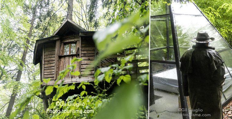 Cabane perchée et personnage de dos devant cabane en verre et forme de pyramide