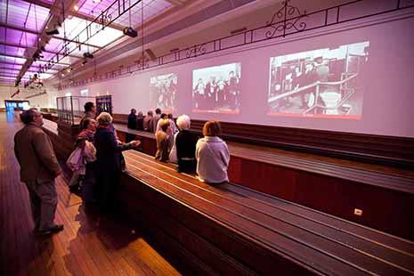 A la Cité de la Mer, le parcours « Titanic, retour à Cherbourg » s'est notablement enrichi. Dans l'ancienne Salle des bagages sont présentés films et expos interactives sur tablettes. (©La Cité de la Mer_B.Almodovar )