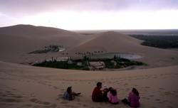 Halte familiale en haut des dunes Mingsha, près de Dunhuang et vue sur « le lac en croissant de lune ».